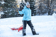 Smiling girl with red sled Royalty Free Stock Image