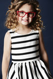 Smiling girl in red spectacles Stock Image