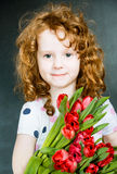 Smiling girl with red tulips Royalty Free Stock Images