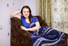 Smiling girl relax at home. Smiling girl relax in the armchair at home Royalty Free Stock Photos