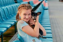 Smiling girl relaxing with dog. girl with her pet on the seats of the stadium stock photo
