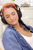 Smiling girl relaxing with music. Smiling girl relaxing with eyes closed, listening to music via headphones, glasses on forehead Royalty Free Stock Image