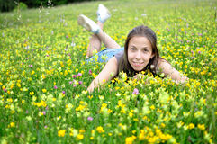 Smiling girl resting on the green grass and flower Royalty Free Stock Images