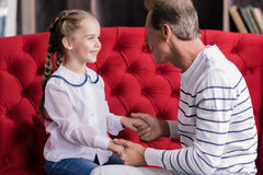 Smiling girl resting with her grandfather Stock Image