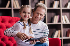 Smiling girl resting with her grandfather and holding the tablet Stock Images