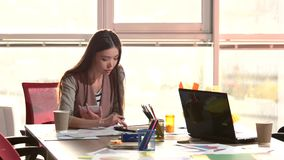 Smiling girl rewriting info from tablet in notebook. Office girl holding notepad and writing down info from tablet screen stock footage