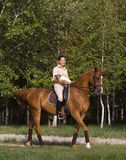 Smiling girl rides a horse with dog Royalty Free Stock Image