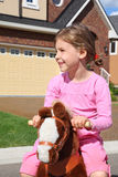 Smiling girl rides at toy horse near cottage Stock Images
