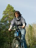 Smiling girl riding on bicycle. Smiling girl riding on a bicycle in the forest wheel blur Stock Images