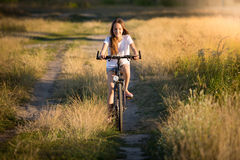 Smiling girl riding on bicycle in meadows at sunset Stock Photography