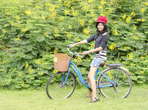 Smiling girl riding a bicycle in the park Stock Photo