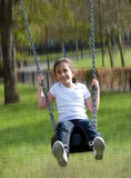 Smiling girl riding a swing Royalty Free Stock Photography