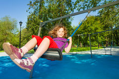 Smiling girl riding swings on the playground Stock Photography