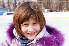 Smiling girl on rink in sunny winter day Royalty Free Stock Image