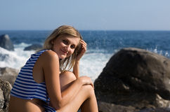 Smiling girl on rocky beach by the sea. Stock Images