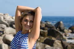 Smiling girl on rocky beach by the sea. Royalty Free Stock Image