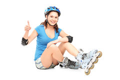 A smiling girl with roller skates giving a thumb up Stock Photo