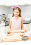 Smiling girl rolling dough on messy kitchen. Cute smiling girl rolling dough on messy kitchen Royalty Free Stock Images