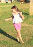 Smiling girl running barefoot Stock Photo
