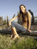 Smiling Girl in Rustic Environment. A pretty girl sitting on a gate, smiling Royalty Free Stock Photo