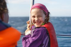 Smiling girl in safety jacket on a boat trip. Family on a blue whale watching trip stock photo