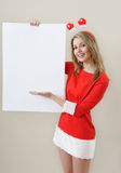 Smiling girl in santa claus clothes hold empty blank banner with Royalty Free Stock Images