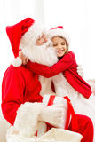 Smiling girl with santa claus and gift at home Stock Photos
