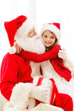 Smiling girl with santa claus and gift at home Stock Photo