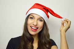 Smiling girl with Santa Claus hat on gray background stock images