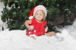 Smiling girl in santa costume sits on snow royalty free stock images