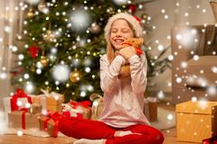 Smiling girl in santa hat with christmas gift royalty free stock photo