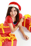 Smiling girl with santa hat and christmas gifts Stock Image