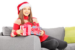 Smiling girl with santa hat on a couch holding a gift Royalty Free Stock Photos
