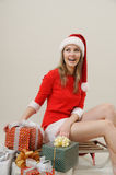 Smiling girl in Santa hat with gifts for Christmas Stock Image