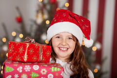 Smiling girl in a Santa hat with her gifts Stock Photos