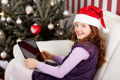 Smiling girl in a Santa hat with a laptop Royalty Free Stock Photo