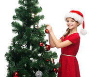 Smiling girl in santa helper hat decorating a tree Stock Photography
