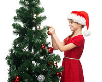 Smiling girl in santa helper hat decorating a tree Royalty Free Stock Photography