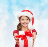 Smiling girl in santa helper hat with gift box Royalty Free Stock Photo