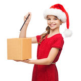 Smiling girl in santa helper hat with gift box Royalty Free Stock Photography