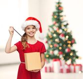 Smiling girl in santa helper hat with gift box Stock Image