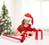 Smiling girl in santa helper hat with gift box Stock Photos