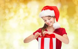 Smiling girl in santa helper hat with gift box Royalty Free Stock Images