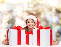 Smiling girl in santa helper hat with gift boxes Royalty Free Stock Photography