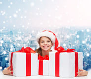 Smiling girl in santa helper hat with gift boxes Stock Photos