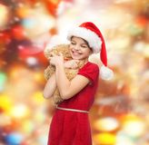 Smiling girl in santa helper hat with teddy bear Royalty Free Stock Photos