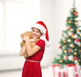 Smiling girl in santa helper hat with teddy bear Stock Photo