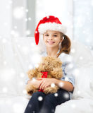 Smiling girl in santa helper hat with teddy bear Royalty Free Stock Images