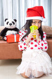 Smiling girl in santa helper hat with teddy bear Stock Photos