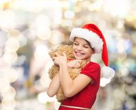 Smiling girl in santa helper hat with teddy bear Royalty Free Stock Photography